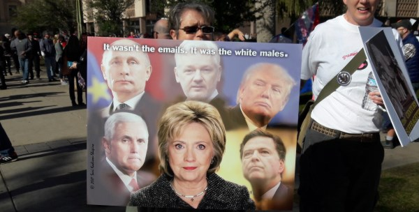 Woman holding sign: It wasn't the emails. It was the white males.